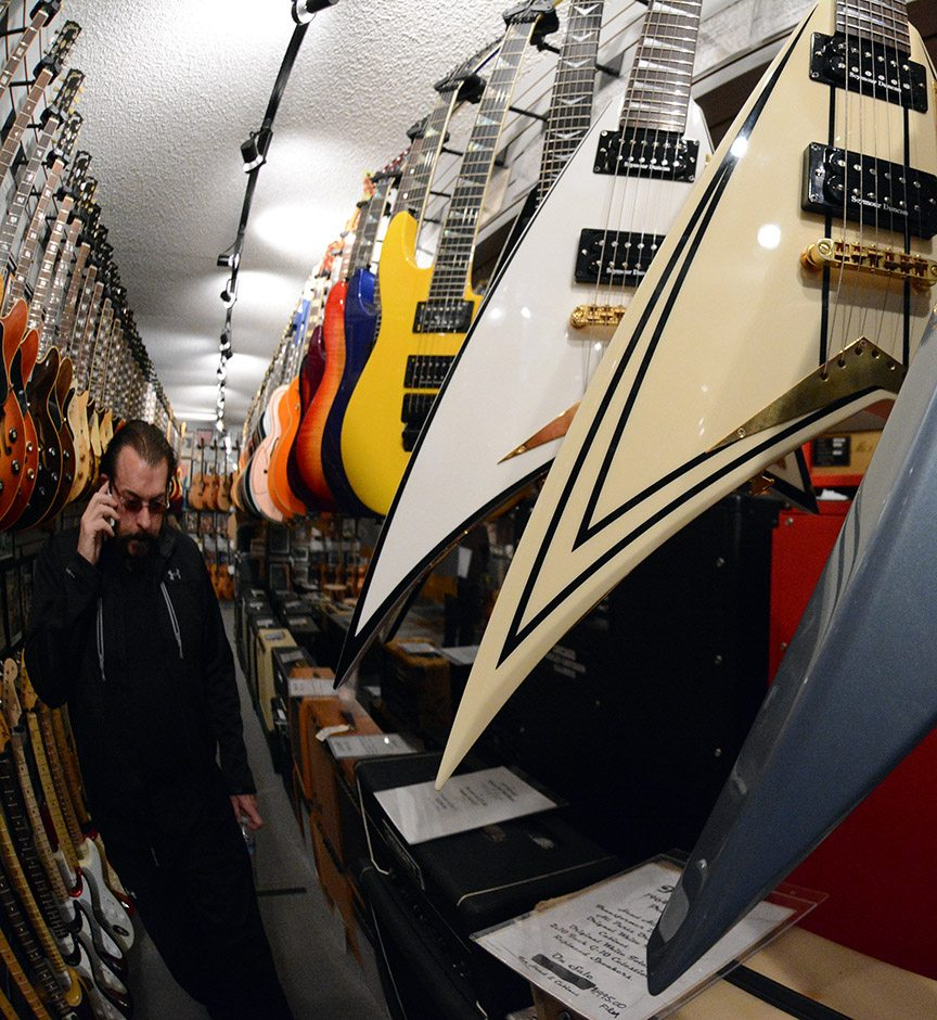 Greg Golden takes a call on  the Flying V aisle in the vault at Bizarre Guitar in north Reno. Tim Parsons/ Tahoe Onstage