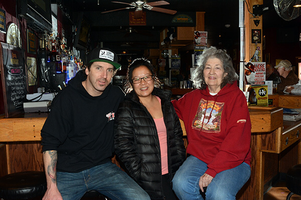 New Whiskey Dick's Saloon owners Adrian Mills, left, and Mei Wormkessel are with former owner Jan