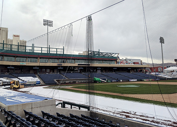 After a snowfall, nets go up at Greater Nevada Field.
